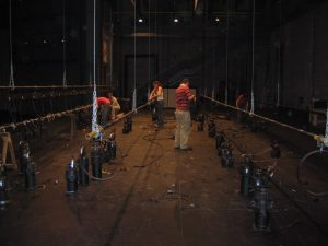 Photo of stage technicians working.  There are multiple battens lowered all the way to the deck.  They are hanging large lighting instruments on them and running cable.