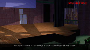 """Image of an empty stage seen from the audience.  The fly rail is visible in the wings, and some scenery pieces.     A label in the corner reads """"Non-Public Space."""""""