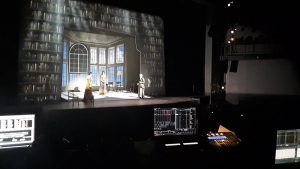 View of a stage during a technical rehearsal.  Various monitors and light boards are visible in the foreground.  Three actors in period costume stand on a raked stage with projected scenery around it.