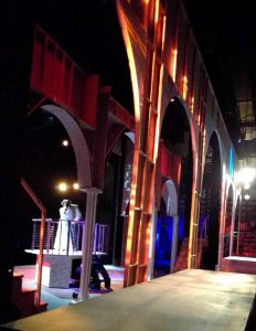 View from backstage of a technical rehearsal in progress.   Several wood arched drops are in place with platforms.  Lights are visible across the stage.