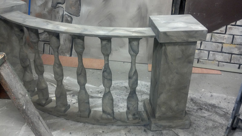 A curved balustrade railing unit in a scene shop.  It has marble texture in gray tones.