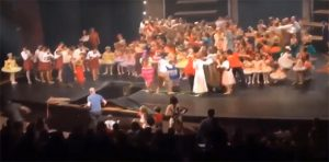 Image of a stage with many children and teenagers.   Part of the stage has collapsed and many have fallen through the hole.