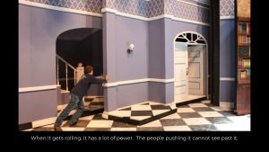 Image of rolling pieces of scenery with walls, floors, stairs, and doors.  A crew member is leaning heavily into one unit to push it forcefully.